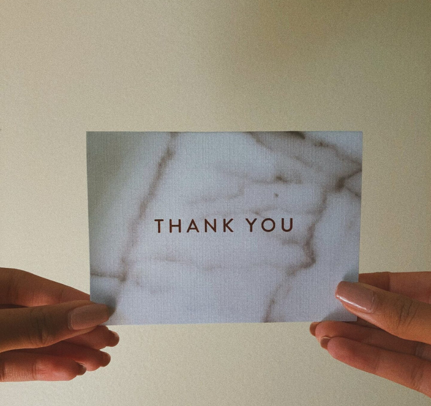 a girl holding a thank you note in her hand
