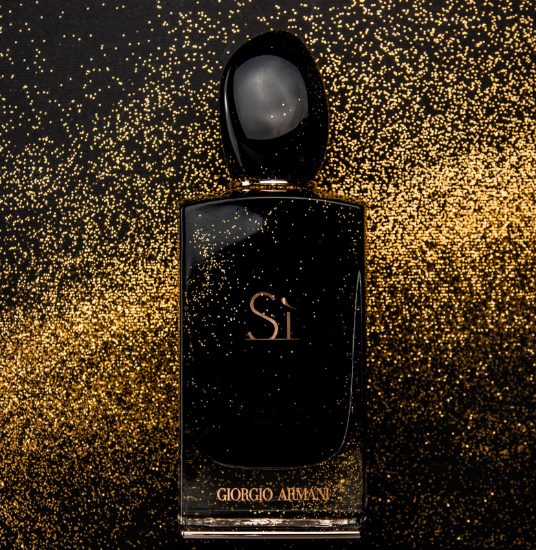 a image of a fragrance bottle with a background of gold specks | What's the Difference Between Eau de Toilette and Eau de Parfum