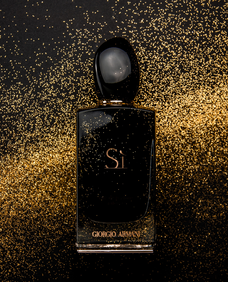 a image of a fragrance bottle with a background of gold specks | What's the Difference Between Eau de Toilette and Eau de Perfume