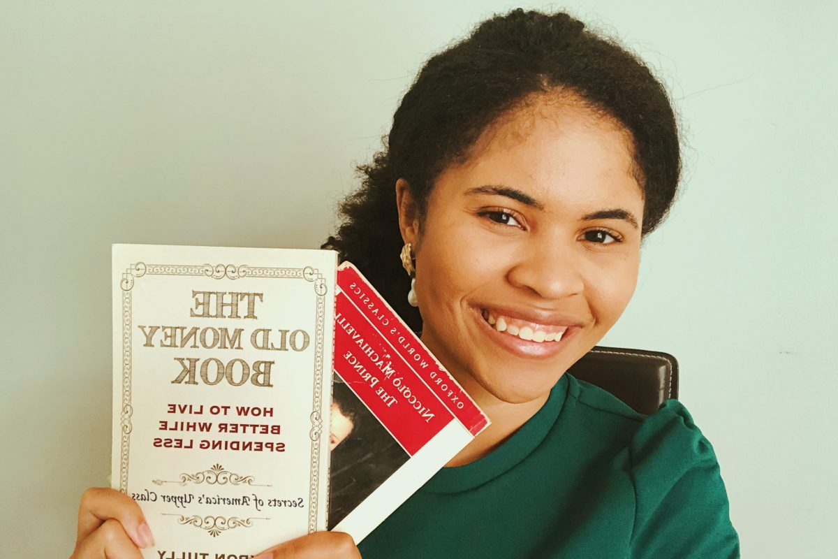 a photo of a black girl smiling with two books in her hand